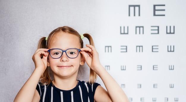 Счастливая маленькая девочка в очках сдает тест на зрение перед школой с размытой диаграммой зрения на заднем плане, медицинский осмотр в детском саду и школе