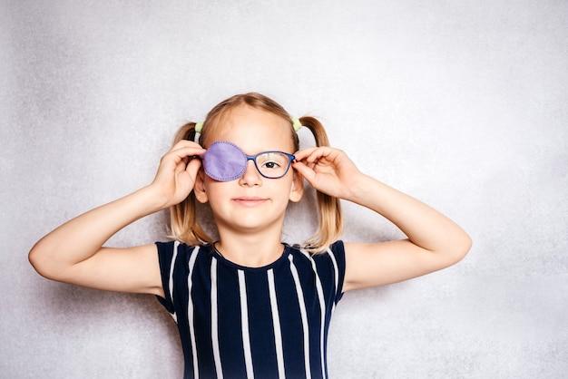 Счастливая маленькая девочка в очках и повязке на глаз или окклюдер, лечение амблиопии (ленивого глаза)