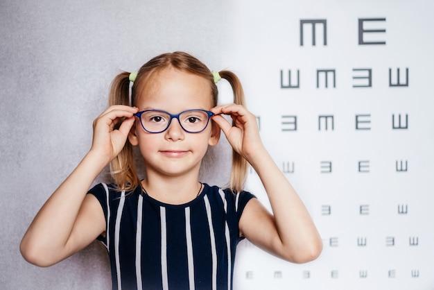Счастливая маленькая девочка в очках сдает тест на зрение перед школой с размытой диаграммой зрения на заднем плане, проверка зрения ребенка