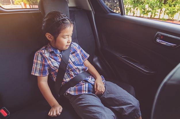 Happy little girl wearing seatbelts in car