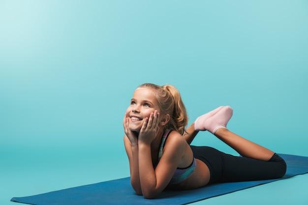 Счастливая маленькая девочка в спортивной одежде делает упражнения на фитнес-коврике, изолированной над синей стеной