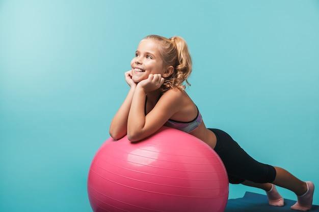 Счастливая маленькая девочка в спортивной одежде делает упражнения с фитнес-мячом, изолированным над синей стеной