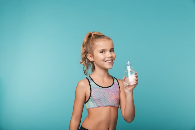 Happy little girl wearing sport clothing drinking water from a bottle isolated over blue wall