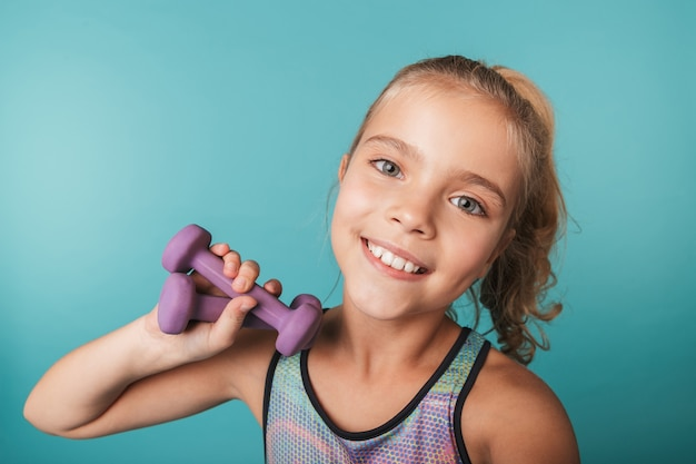 Happy little girl wearing sport clothing holding small dumbbells isolated over blue wall