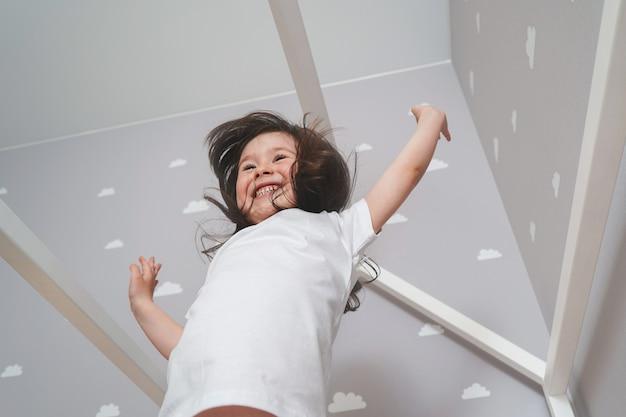 白い寝室のベッドの上をジャンプ白のパジャマを着て幸せな少女。ジャンプしながら遊ぶかわいい女の子