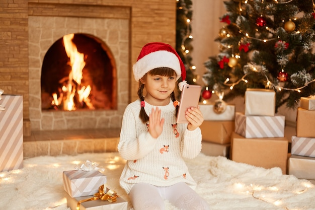 Happy little girl wearing white sweater and santa claus hat, posing in festive room with fireplace and xmas tree, waving hand to cellphone camera, having video call.