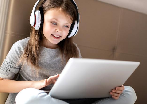 Happy little girl in wireless headphones joyfully using laptop at home