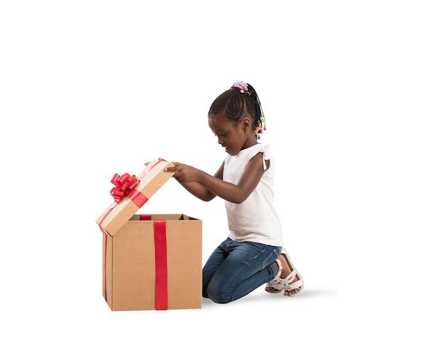 Счастливая маленькая девочка с большим рождественским подарком
