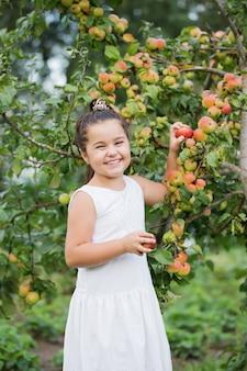果樹園でリンゴと幸せな少女