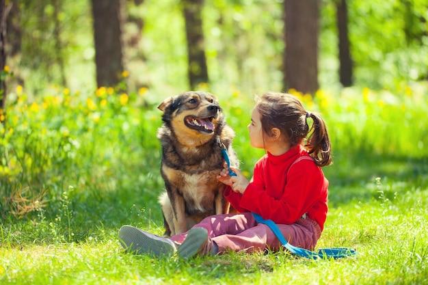 Счастливая маленькая девочка с большой собакой, сидящей на лужайке