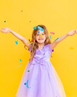 ブロンドの髪と青いドレスを着た幸せな少女は、黄色の背景、休日の概念で紙吹雪をキャッチ