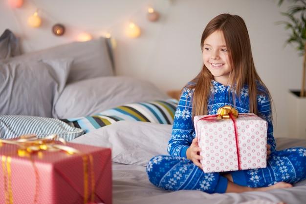 Счастливая маленькая девочка с рождественским подарком