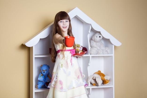 Счастливая маленькая девочка с чашкой чая в своей комнате