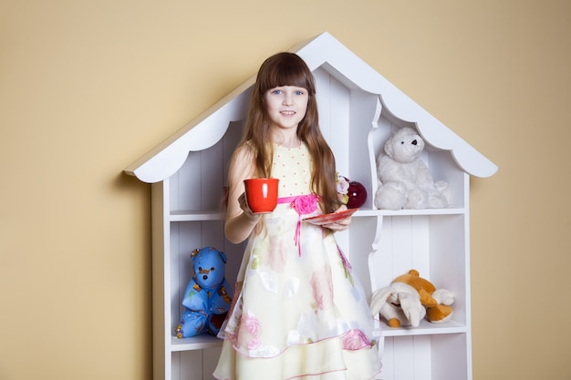 Happy little girl with cup of tea in her room