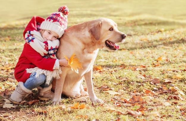 Счастливая маленькая девочка с собакой в осеннем парке