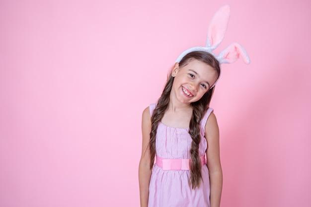 スタジオピンクの背景のコピースペースでポーズをとってイースターバニーの耳を持つ幸せな少女。イースター休暇のコンセプト。