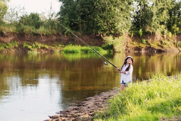여름 강에 낚 싯 대와 함께 행복 한 어린 소녀