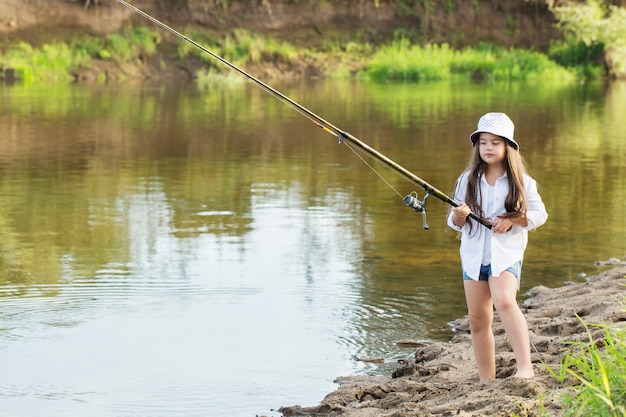 Happy little girl with fishing rod on summer river