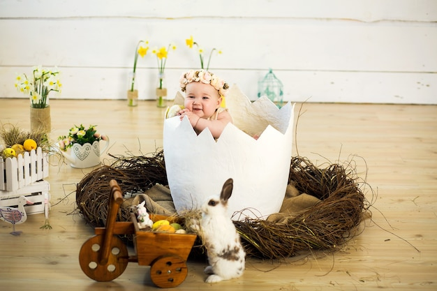 A happy little girl with flowers on her head is sitting in a decorative egg. easter egg in the studio scenery.