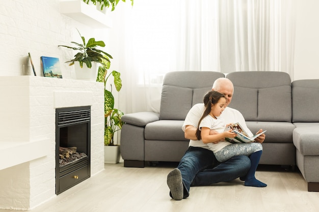Happy little girl with grandfather reading story book at home