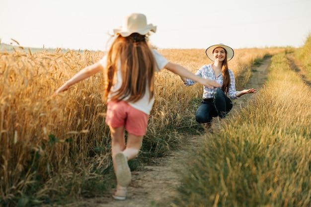 Счастливая маленькая девочка в шляпе на голове бежит к матери рядом с пшеничным полем семья фермеров ...