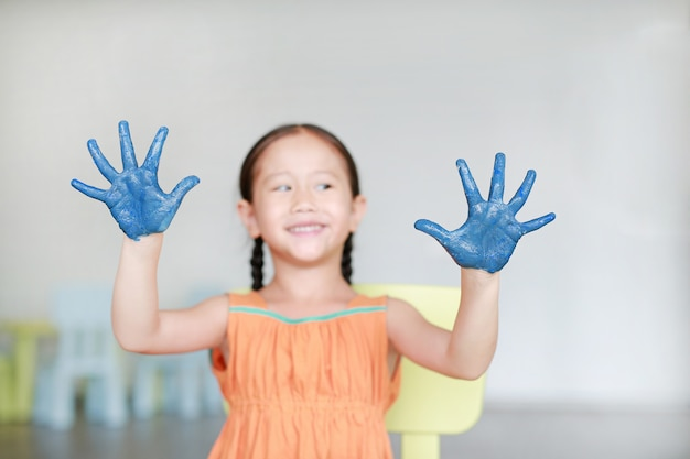 Happy little girl with her blue hands in the paint in children room. focus at baby hands.