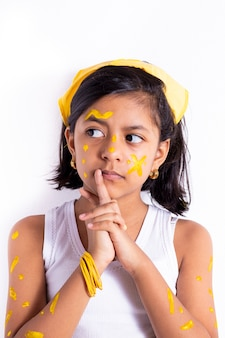 Happy little girl, with her face painted to celebrate the yellow day