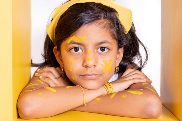 Счастливая маленькая девочка с раскрашенным лицом, чтобы отпраздновать желтый день