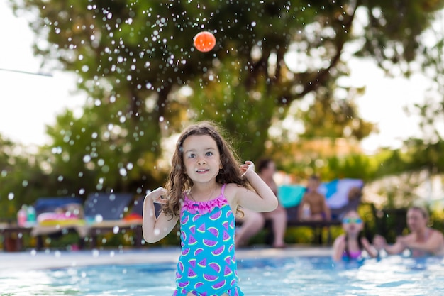 Happy little girl with her hair down in a bright swimsuit playing ball in the pool on a sunny summer day