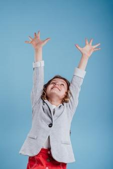 파란 배경에 격리된 승리를 즐기며 손을 들고 있는 행복한 어린 소녀