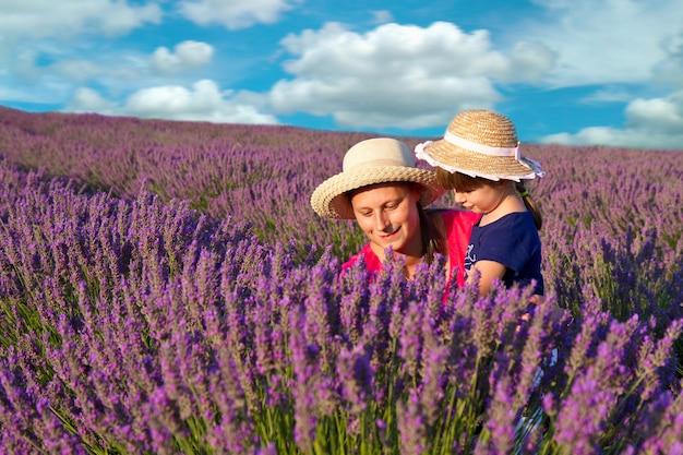 Счастливая маленькая девочка со своей матерью в лавандовом поле
