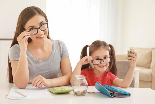 실내 테이블에 앉아 그녀의 어머니와 함께 행복 한 어린 소녀. 돈 저축 개념