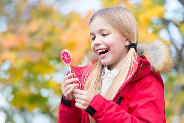 가 공원에서 롤리팝과 함께 행복 한 어린 소녀입니다. 막대기에 막대 사탕과 함께 웃는 행복 어린 소녀. 가을은 단풍을 바꿉니다. 달콤한 분위기.
