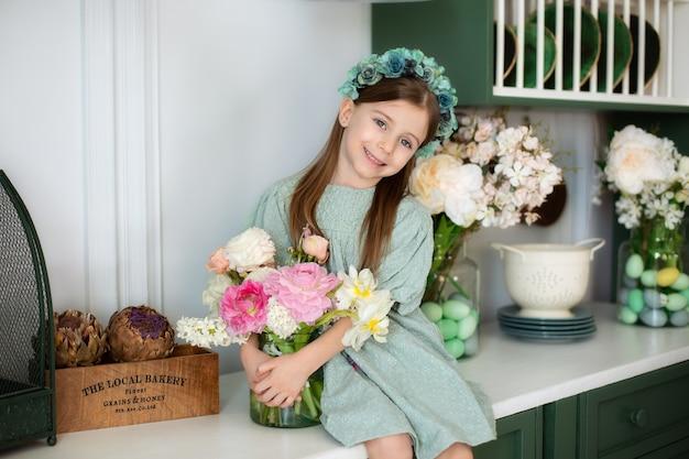Счастливая маленькая девочка с длинными волосами держит букет цветов на кухне празднование дня матери