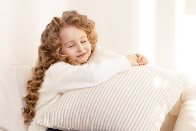 枕を抱き、笑顔の長い髪の幸せな少女
