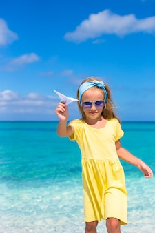 Happy little girl with paper airplane in hands on white sandy beach