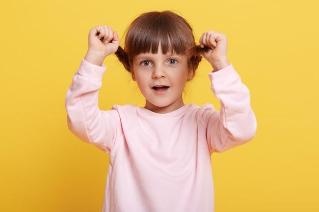 열린 된 입으로 카메라를 직접보고, 그녀의 머리띠에 손을 유지, 옅은 분홍색 캐주얼 복장을 입고, 노란색 배경 위에 절연 포즈와 함께 행복 한 어린 소녀.
