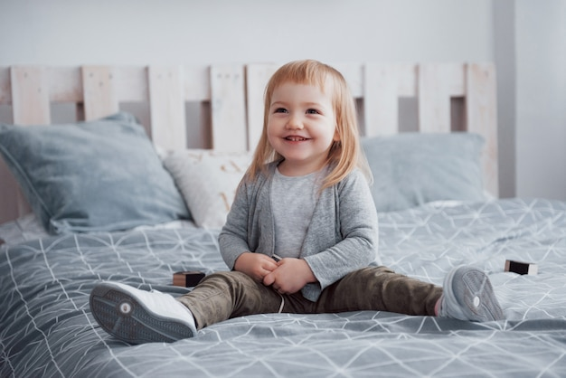 Happy little girl with a pillow in bed at home
