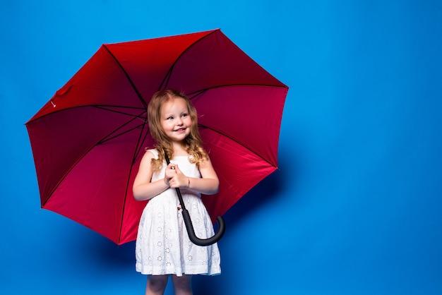 Bambina felice con l'ombrello rosso che posa sulla parete blu. Foto Gratuite