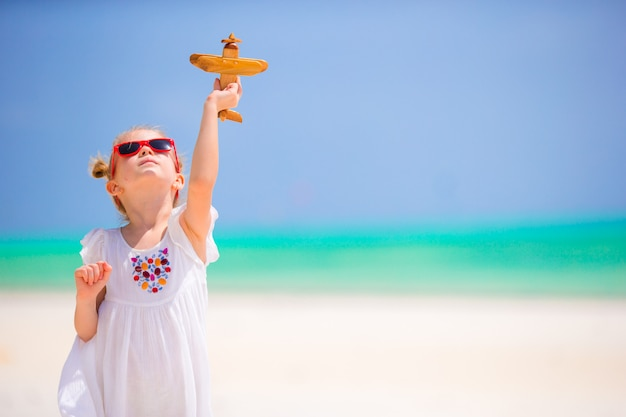 Happy little girl with toy airplane in hands on white sandy beach. photo travel advertising, flights and airlines