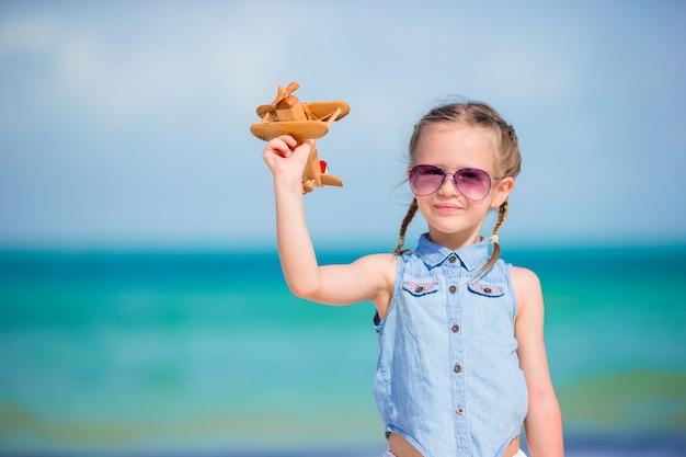 白い砂浜のビーチで手でおもちゃの飛行機との幸せな女の子