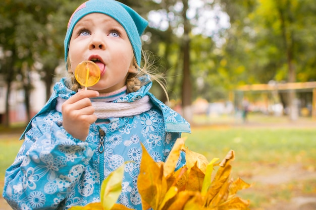 Happy little girl with with bouquet of autumn leaves in the park