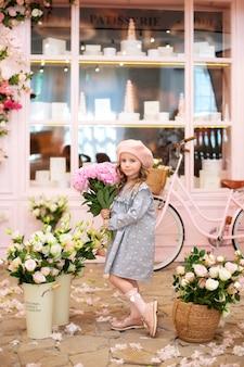 牡丹の花束を持つ幸せな少女は、通りのカフェの近くに立っています。母の日。お祝い。