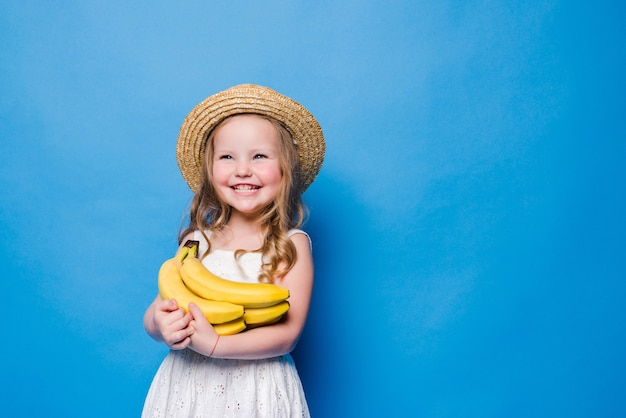 青い壁に分離された黄色のバナナと幸せな少女