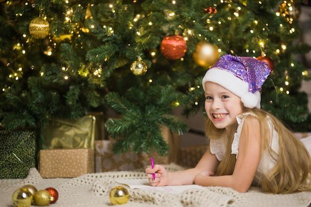 飾られたクリスマスの部屋でサンタに手紙を書く幸せな少女