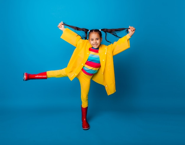 Happy little girl in a yellow raincoat and red boots on a blue background.