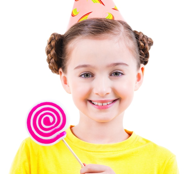 Bambina felice in maglietta gialla e cappello del partito che tiene caramelle colorate - isolato su bianco.