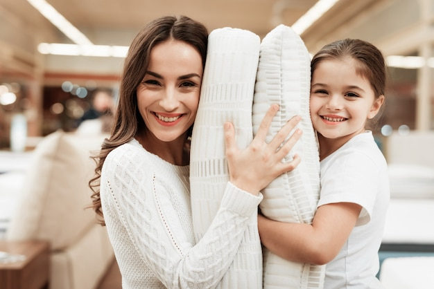 Happy little girl and young woman hugging pillows