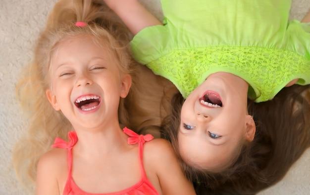 幸せな女の子の金髪とブルネットは仰向けになって笑っています。上面図。