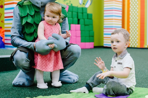 幸せな小さな女の子、男の子、誕生日パーティーのためのゲームの子供部屋でおもちゃを遊んでいる子供たち。キッズアミューズメントパークとプレイセンターは屋内にあります。エンターテインメントセンターで一緒に時間を過ごしましょう。